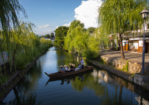 Tourists enjoying a cruise on a small boat on the river in Bikan historical quarter