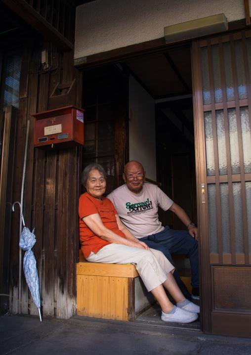 Smiling japanese couple sit in the entrance of their wooden house, Okayama Prefecture, Kurashiki, Japan
