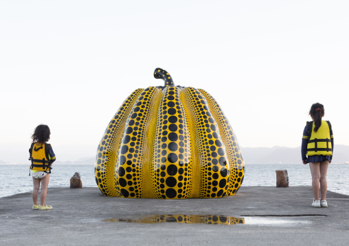 Children standing on the sides of the yellow pumpkin by Yayoi Kusama on pier at sea, Seto Inland Sea, Naoshima, Japan