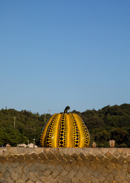 Yellow pumpkin by Yayoi Kusama on pier at sea, Seto Inland Sea, Naoshima, Japan