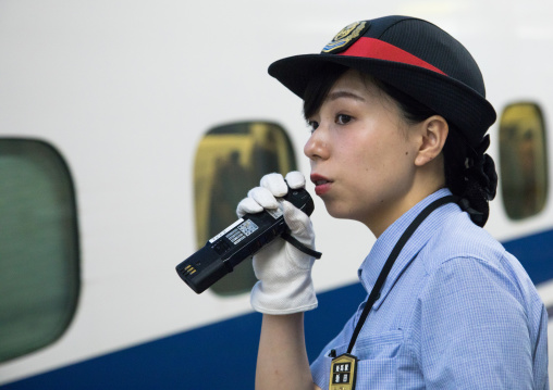 Japanese female station master speaking in a microphone in front of a Shinkansen train in a station, Hypgo Prefecture, Himeji, Japan