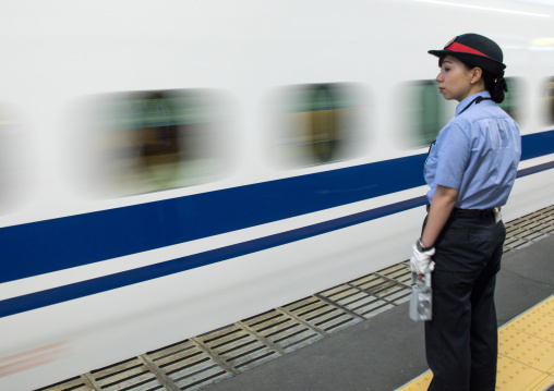 Japanese female station master in front of a Shinkansen train in a station, Hypgo Prefecture, Himeji, Japan