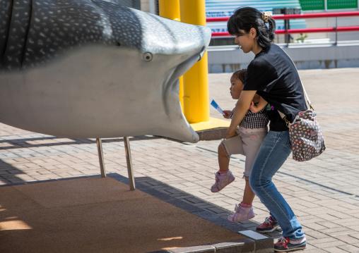 Mother holding her child to let her inside a fake giant plastic whale shark in Kaiyukan aquarium, Kansai region, Osaka, Japan