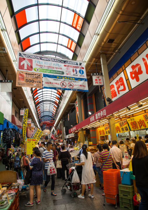 Shoppers walk along Kuromon Ichiba market, Kansai region, Osaka, Japan