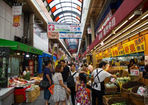 Shoppers walk along Kuromon Ichiba market, Kansai region, Osaka, Japan