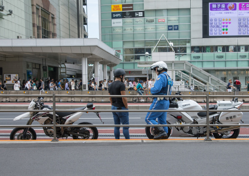 Police control traffic with a motorbike driver, Kanto region, Tokyo, Japan