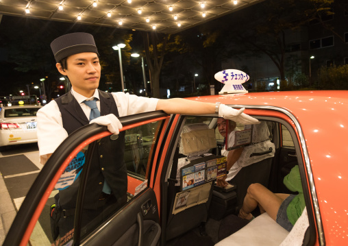 Japanese hotel employee opens taxi door and put his hand to avoid head shock, Kanto region, Tokyo, Japan