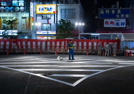 Police man in the street at night, Kanto region, Tokyo, Japan