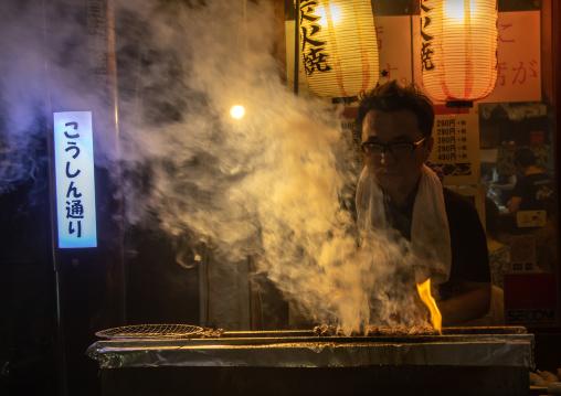 Vendor preparing food on barbecue grill at street market, Kanto region, Tokyo, Japan