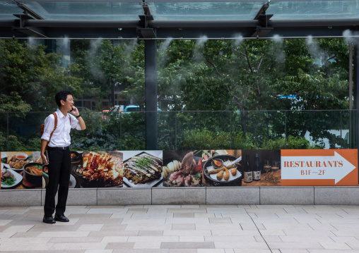 Japanese man on the phone searching for freshness under a water spray, Kanto region, Tokyo, Japan