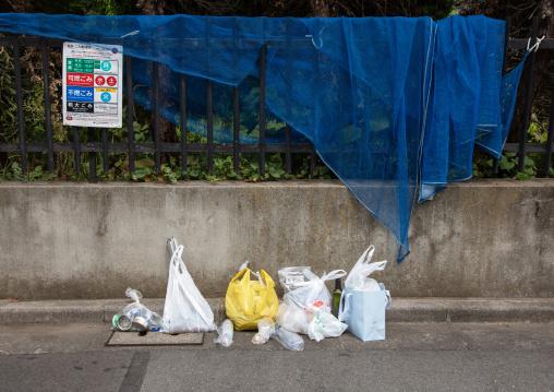 Rubbish on street in plastic bags, Kanto region, Tokyo, Japan