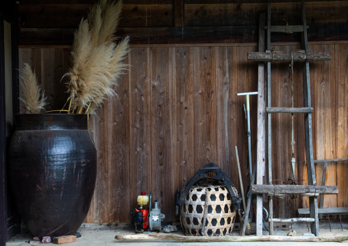 Huge jar in front of a wooden house, Kyoto Prefecture, Miyama, Japan