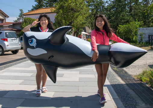 Japanese tourists carrying an orca shaped inflatable ring in Amanohashidate sanbar, Kyoto Prefecture, Miyazu, Japan