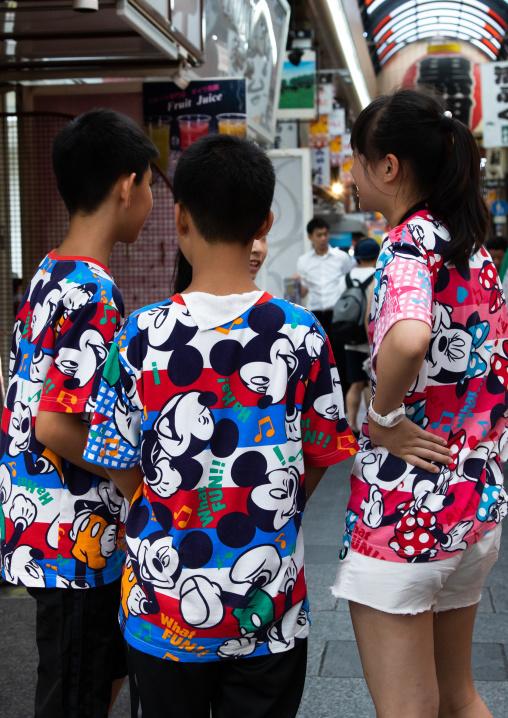 Teenagers in the street wearing Mickey mouse shirts, Kansai region, Osaka, Japan