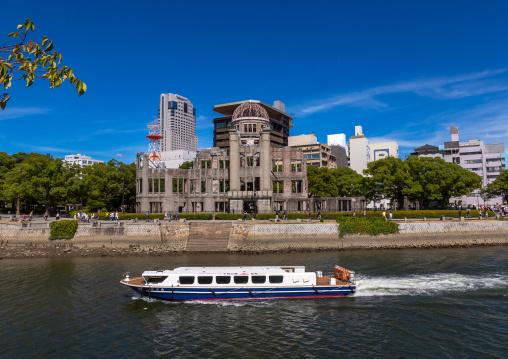 Ferry boat in ota river in front of the Genbaku dome in Hiroshima peace memorial park, Chugoku region, Hiroshima, Japan