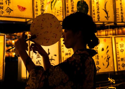 Japanese woman in yaukuta during Gokoku shrine Mitama matsuri Obon festival celebrating the return of the spirits of the deads, Kyushu region, Fukuoka, Japan
