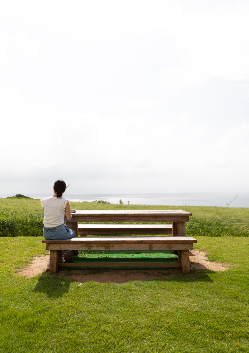 Lonely woman sit on a bench, Yaeyama Islands, Ishigaki-jima, Japan