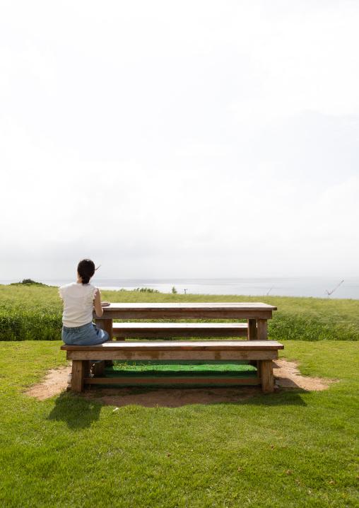 Lonely woman sit on a bench, Yaeyama Islands, Ishigaki-jima, Japan
