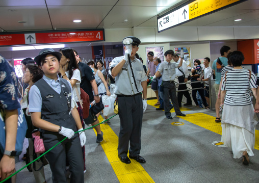 Policeman with megaphone in the subway, Kanto region, Tokyo, Japan