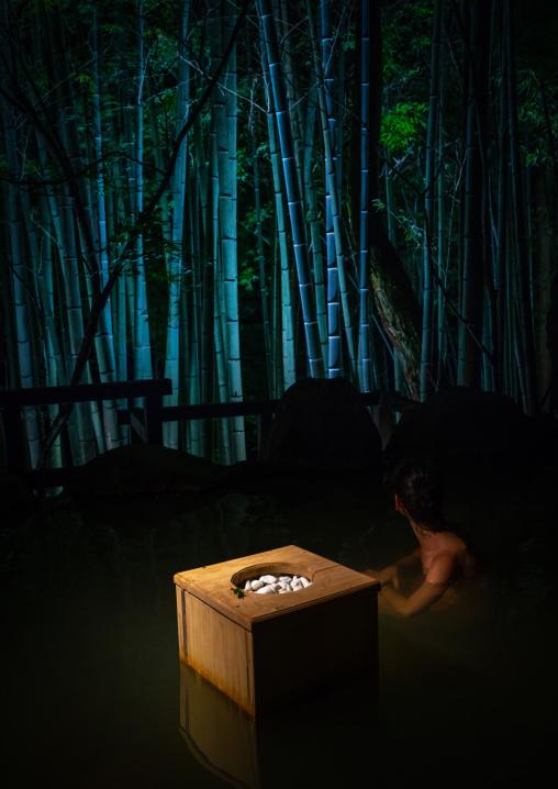 Woman bathing at hot spring next to a bamboo forest in Takefue ryokan, Kumamoto Prefecture, Minamioguni-machi, Japan