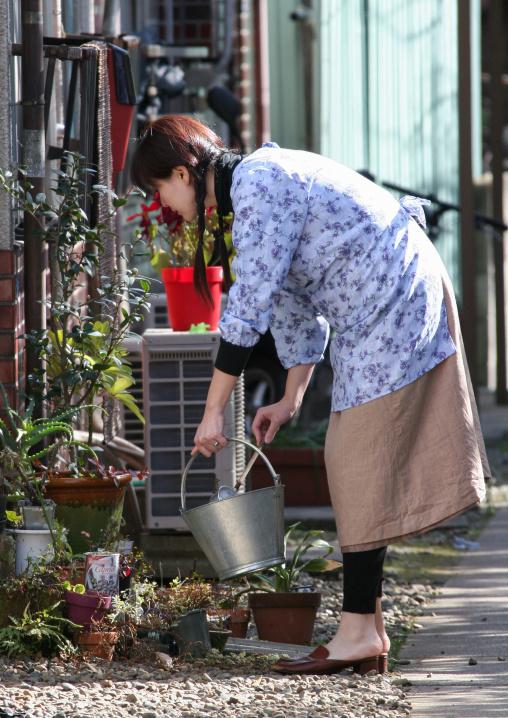 Japanese woman watering her plants, Kanto region, Tokyo, Japan