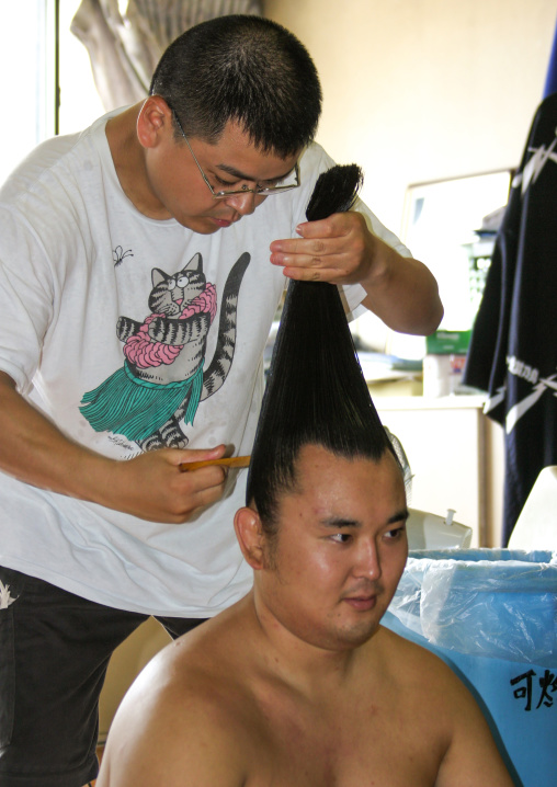 Hairdresser making a bun to a sumo wrestler, Kanto region, Tokyo, Japan