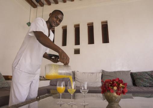 Waiter serving fruit juice in forodhani house, Lamu county, Shela, Kenya