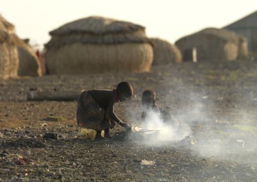Grass huts and children making fire in el molo tribe village, Turkana lake, Loiyangalani, Kenya