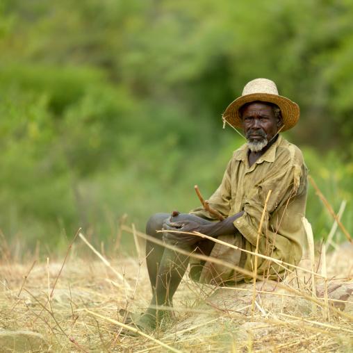 Tharaka old man with a hat sit in the bush, Laikipia County, Mount Kenya, Kenya