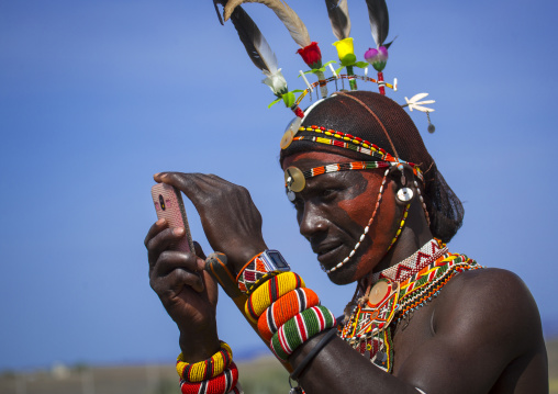Rendille tribesman taking picture with his mobile phone, Turkana lake, Loiyangalani, Kenya