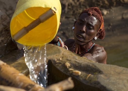 Rendille tribe man taking water in a singing well for his camels, Marsabit district, Ngurunit, Kenya