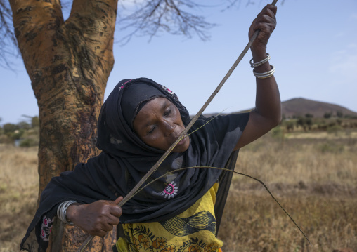 Borana woman cutting wood with her teeth to build a house, Marsabit district, Marsabit, Kenya