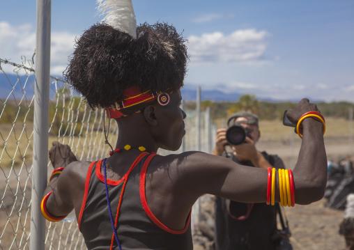 Turkana tribesman taking pictures in front of tourists, Turkana lake, Loiyangalani, Kenya