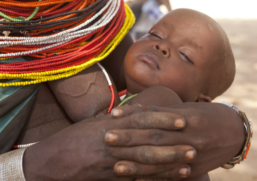 Rendille tribeswoman holding her sleeping baby, Marsabit district, Ngurunit, Kenya