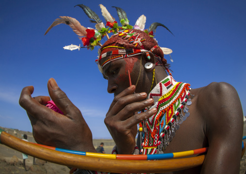 Rendille tribesman applying make up, Turkana lake, Loiyangalani, Kenya