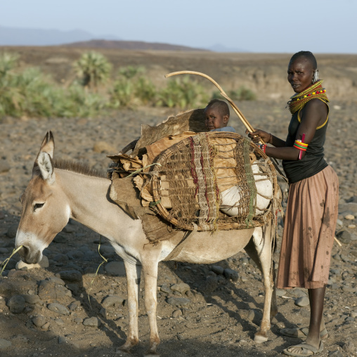 Rendille tribe woman with her baby sit a donkey, Rift Valley Province, Turkana lake, Kenya