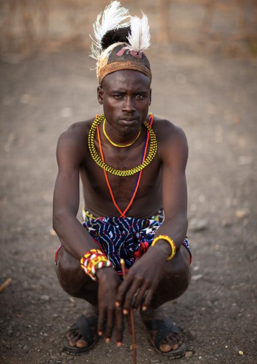 Portrait of a Turkana tribe man squatting with ostrich feathers on the headwear, Rift Valley Province, Turkana lake, Kenya