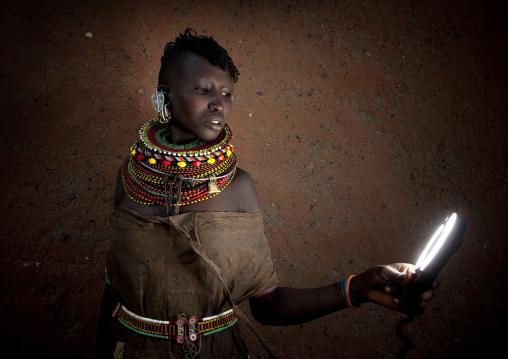 Turkana tribe woman with huge necklaces and earrings looking at a torch, Turkana lake, Loiyangalani, Kenya