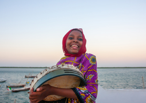 Portrait of a smiling swahili girl playing drum, Lamu County, Lamu, Kenya
