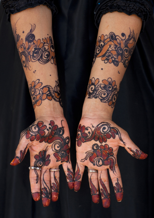Human palm of hand and forearm of woman drawing patterns with henna and indigo blue, Maulidi festival, Lamu kenya