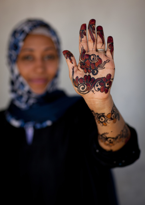 Unrecognizable young woman showing palm of her hand painted with henna and indigo blue, Lamu, Kenya