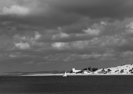 A view on the coast with fort hotel in background and sailing dhow, Lamu, Kenya