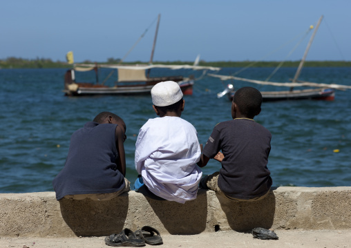 Three little muslim boys chatting alongside the dockside, Dhows in background, Lamu, Kenya
