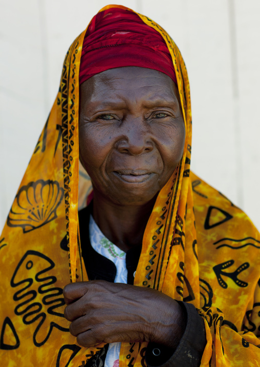 Mid adult woman wearing yellow veil portrait, Lamu, Kenya