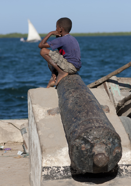 Cannon and dreamy boy on a dockside of lamu kenya