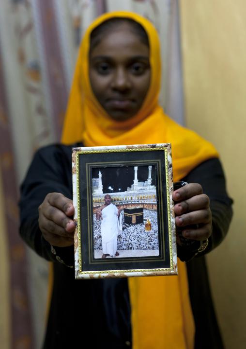 Teenage girl showing picture of father haj to mecca, Lamu County, Lamu, Kenya