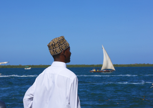 Man with kofia, Looking towards the sea, Dhow passing in the channel, Lamu, Kenya