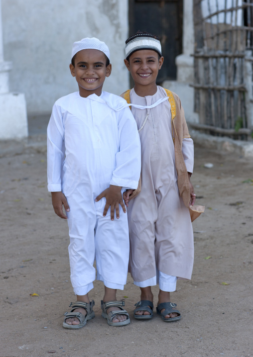 Two young boys traditional dressing looking at camera with amusing smiles, Lamu, Kenya