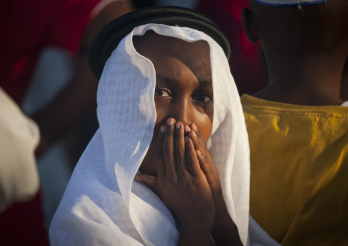 Young boy hiding mouth with hands during malidi procession, Lamu, Kenya
