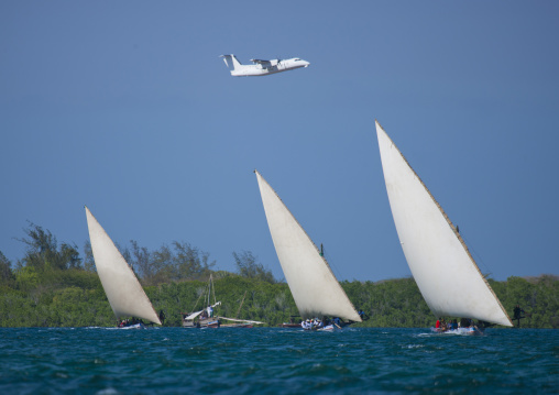 A plane passing above while dhows racing in channel, Lamu, Kenya